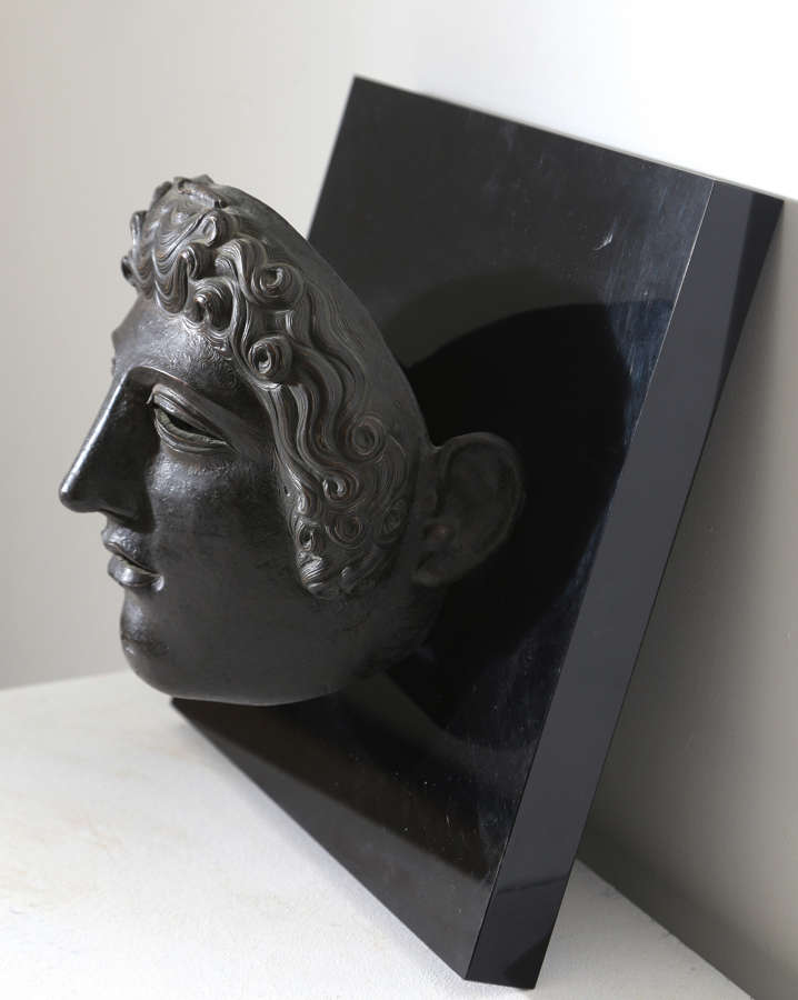 20th century mask of a gladiator mounted on a plaque